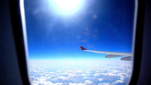 Při pohledu přes okno letadla během letu v křídle s krásnou modrou oblohu a slunce. HD. 1920 x 1080