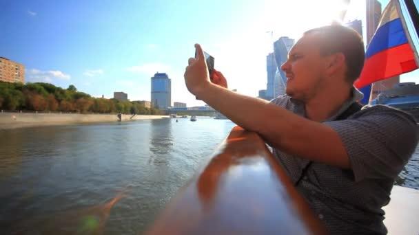 muž vyfotit s smartphone na výletní lodi a mávali vlajkami. HD. 1920 x 1080