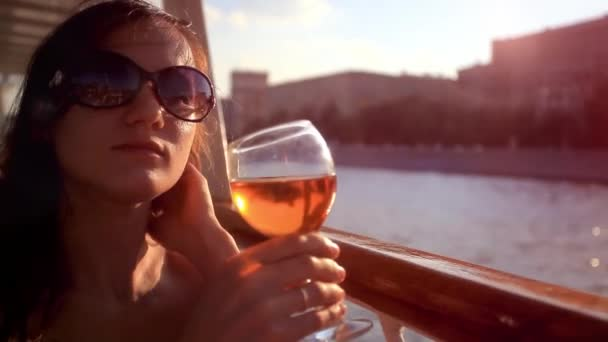 thoughtful woman looking on beautiful sunset with glass of red wine at the cafe table in cruise ship. HD. 1920x1080