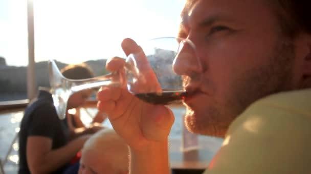 hübscher Mann trinken Wein im Restaurant im Freien auf Luxusyacht, Verkostung Luxus Alkohol trinken. HD 1920 x 1080.