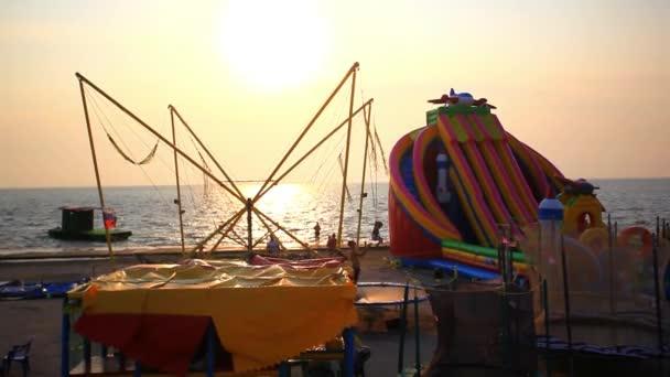 Primorskiy kray, Rusko, 16 srpen, 2014. Děti, skákání na trampolíně při západu slunce na pláži. Nafukovací skluzavky v Jižní město v Rusku