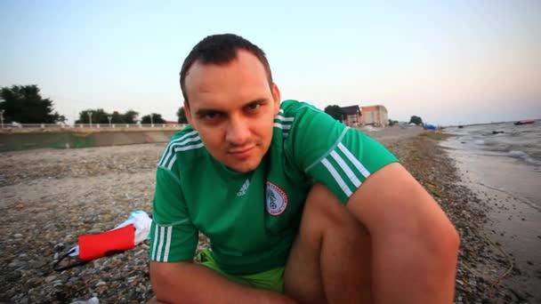 Titokzatos férfi ül a strandon, és úgy néz ki. HD. 1920 x 1080