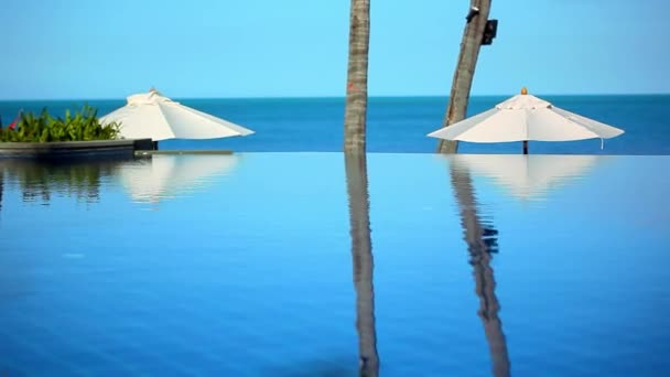 Schwimmbad am Meer auf Grund der blaue Himmel in der Nähe von Strand und weißen Sonnenschirmen. Video UMSCHALT Bewegung Koh Samui Thailand