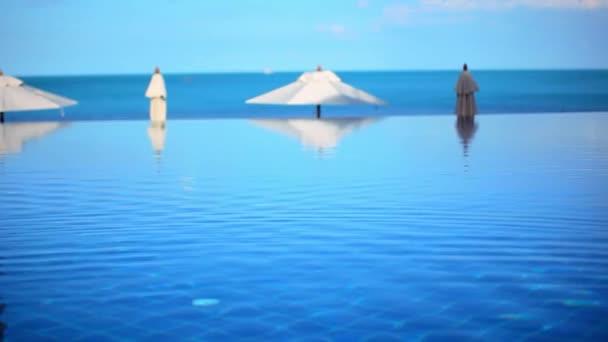 Bazén u moře na pozadí modré oblohy, v blízkosti pláže a bílá deštníky. Pohyb videa posun Koh Samui Thajsko