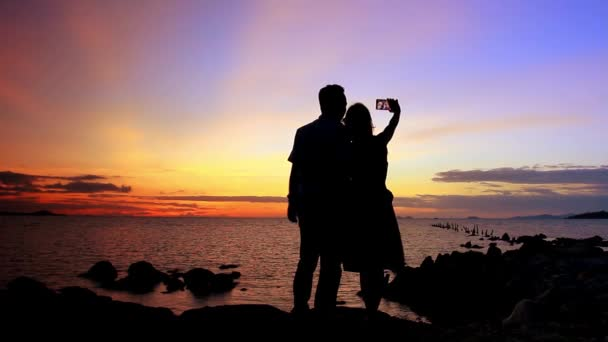 Silhouette couple in love taking self-portrait on the phone against amazing sunset. Video