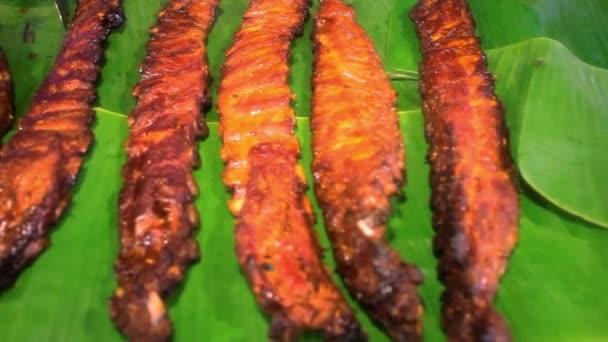 Grilovaná vepřová žebra na zelených listech. Koh Samui pouliční jídlo v Thajsku