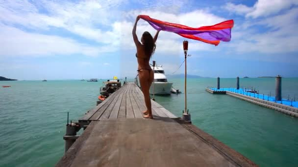 Cute teen girl standing on the bridge with pareo in hands. Koh Samui