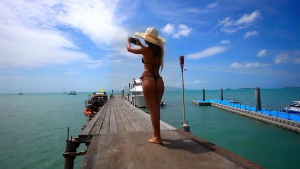 Sexy mladá žena v bikinách a klobouk se obrázek na její mobilní telefon proti oceánem v pozadí