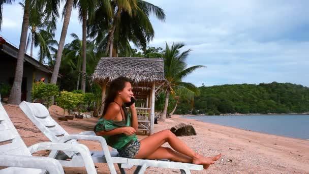 Mladá bruneta žena sedí na lehátko venku na pláži a mluví po telefonu. Koh Samui