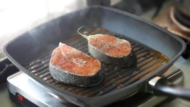 Cooking salmon steaks on the grill pan and lay out on a plate with vegetables. Fast speed of the video