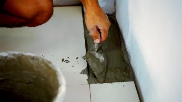 Zblízka mužské ruce pokládce keramické dlažby. Makro video