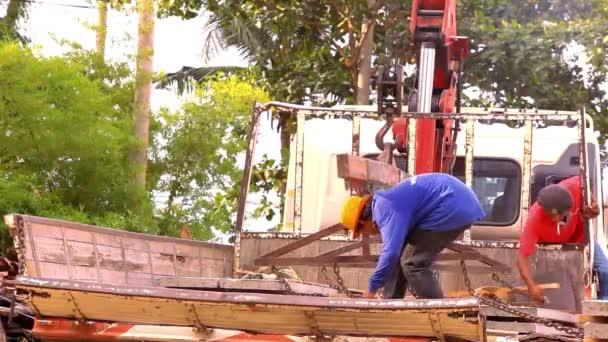 Jeřábnické činnosti na staveništi, pracovníci nesou betonové desky. Video