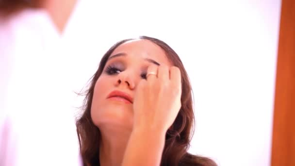 Krásná mladá dívka barvy na oční víčka a řasy na zrcadlo. Video make-upu