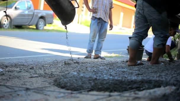 Nalil cementu na silnici a pracovníky zarovnání. Video