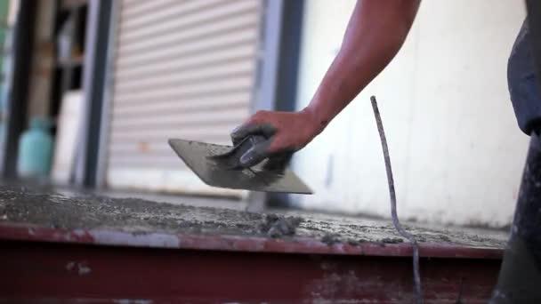 Closeup zednáři ruky šíření betonové směsi s lopatkou. Video
