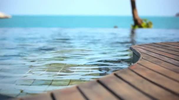 Žena, plavání v bazénu a oceánem na pozadí. Pohyb videa posun