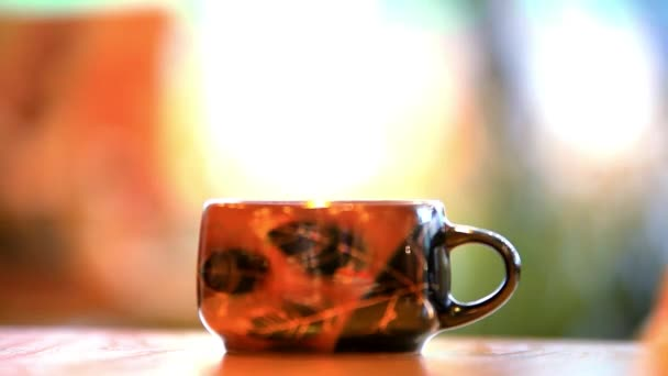 pouring tea into a mug from the pot. HD. 1920x1080. Blurred background with bokeh