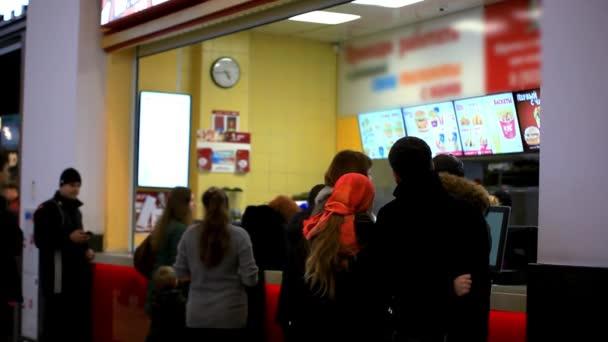 Rusko, Moskva, 12. února 2015, lidé čekají na stravovací služby u Mc Donalds stolu v nákupním středisku. Společnost fast food. HD. 1920 x 1080