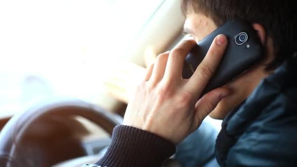 Geschäftsmann mit Handy und digitalem Tablet im Auto bei Sonnenuntergang. hd. 1920x1080