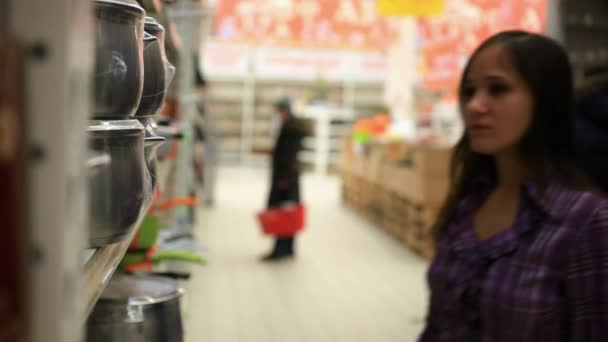Woman with cart shopping buys a pan in supermarket at Kitchenware. HD, 1920x1080