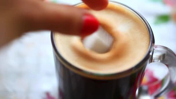 Ruky kostku cukru do šálku kávy a za stálého míchání ji. HD. 1920 x 1080