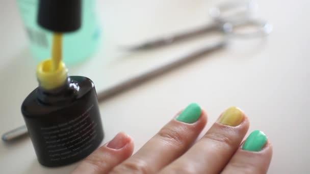 Manikérka dělá jarní manikúra pro ženy v salonu krásy. Zelené a žluté barvy. HD. 1920 x 1080