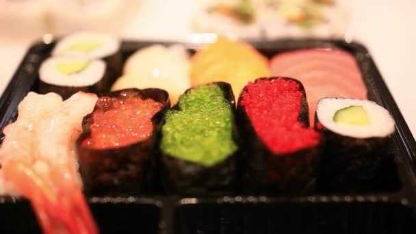 Rozmanitost sushi na policích v supermarketu v Japonsku. Zavřete z makra s rozmazané pozadí a bokeh. HD. 1920 x 1080