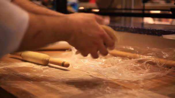 mužské šéfkuchař ruce příprava těsta s váleček pro asijské potraviny na dřevěné desce na kuchyňské lince v pekárně. HD. 1920 x 1080