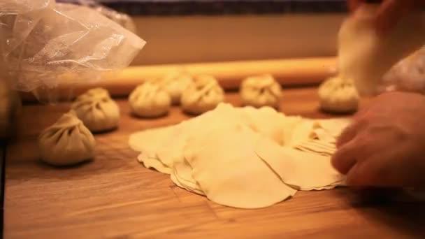 Männliche Köche bereiten Teig mit Nudelholz für asiatische Speisen auf Holzbrettern an der Küchentheke in der Bäckerei zu. hd. 1920x1080