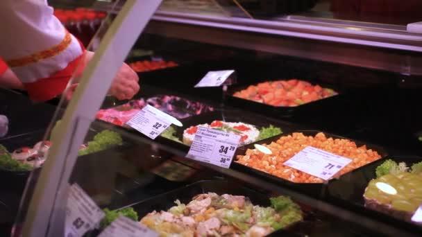 sortiment salátů na vitríny v supermarketu. Žena ruce prodavačka dá salátu na prodej. HD. 1920 x 1080