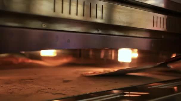 Šéfkuchař klade těsto v troubě pečte pizzy a úzké pece, tradiční vaření. Zblízka. HD. 1920 x 1080