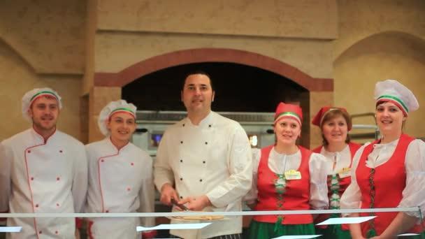 Rusko, Moskva, 7 března 2015, kuchaři prezentovat italskou kuchyni s pizzou na zásobník v kuchyni restaurace. HD. 1920 x 1080