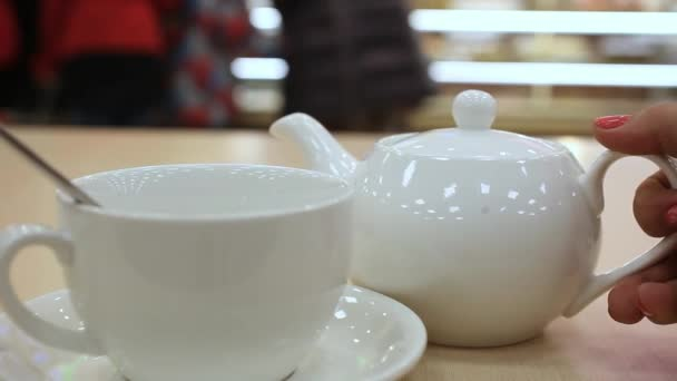 White Teapot pouring tea into a cup. HD. 1920x1080