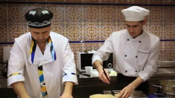 Rusko, Moskva, 7 března 2015, kuchař a kuchař připravuje knedlíčky z mletého masa a těsto s váleček pro asijské potraviny na dřevěné desce na kuchyňské lince v pekárně. HD. 1920 x 1080