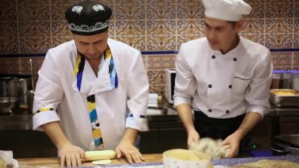 Russland, Moskau, 7. März 2015, lächelt Chef und Koch asiatische Küche auf Holzbrett am Küchentisch in Bäckerei Knödel von Hackfleisch und Teig mit Nudelholz vorbereiten. HD 1920 x 1080.