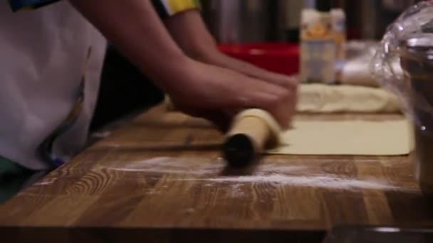 férfi szakácsok keze ázsiai étel a konyhában, és fából készült táblán tésztát sodrófa felkészülés