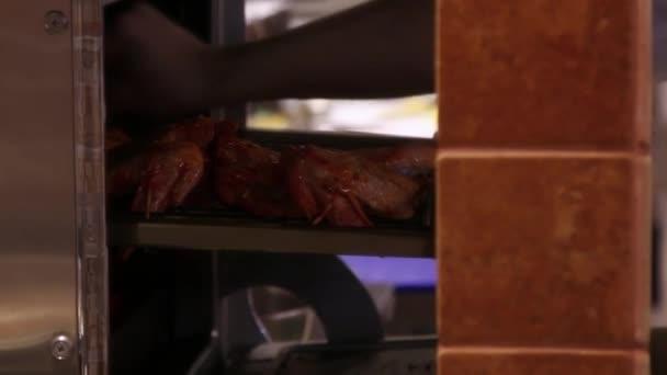 Šéfkuchař dává maso špejle v troubě.