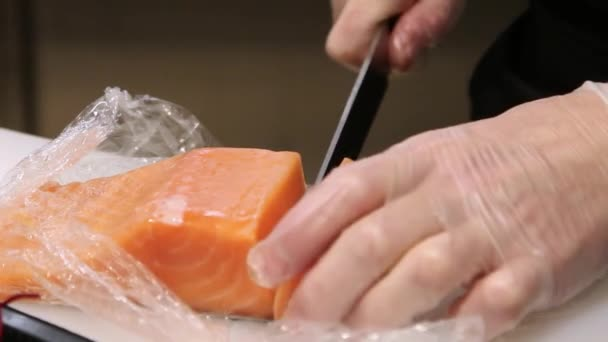 Chefs hands in gloves cutting a fresh salmon on Cutting board and pack fish In kitchen