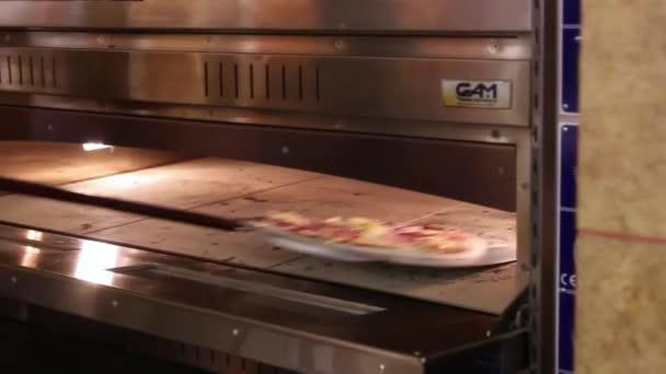 Kuchař dává těsto v troubě pečte pizzy, tradiční vaření v kuchyni restaurace