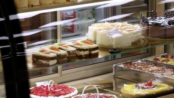 Vitrína na dorty, pečivo v jídelně zobrazení okna pro prodej pouštní Vorarlberska. Dítě se dívá na prezentace