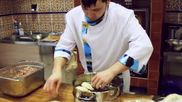 RUSSIA, MOSCOW, 7 MARCH, Chef preparing dough with rolling pin for asian food on wooden board at kitchen counter