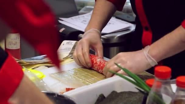 closeup šéfkuchaře ruce v rukavicích vyhrnout suši