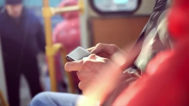 Detail ruce v autobusu člověka pomocí svého mobilního telefonu. Čtení e-mailů. SMS zpráva.