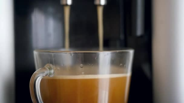 coffe dispenser with cup of coffee. Slowmotion pour