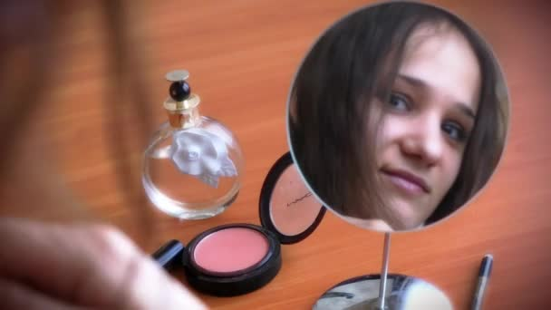 Young beautiful woman  combing hair, paints her lips and smiling before a mirror