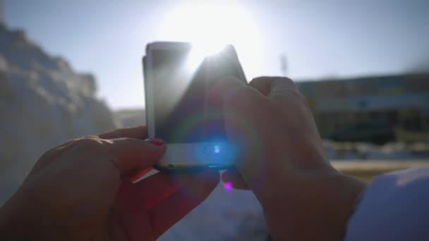 Close Up ruce mladé ženy pomocí smartphone v zimě na pozadí slunce a obloha