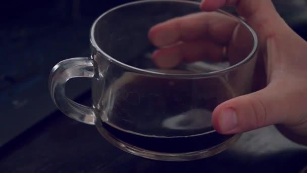 Člověk s použitím počítače při pití šálek kávy na sluneční světlo v noci