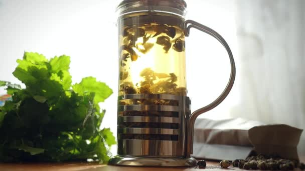 Slowmotion of glass teapot with blooming tea flower inside. Brewing tea in boiling water