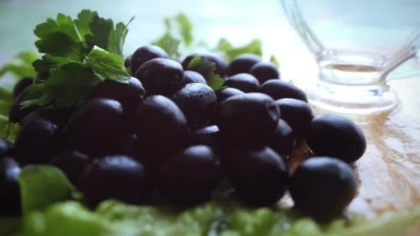 Zpomalený pohyb láhev nalil panenský olivový olej v misce vedle olivy