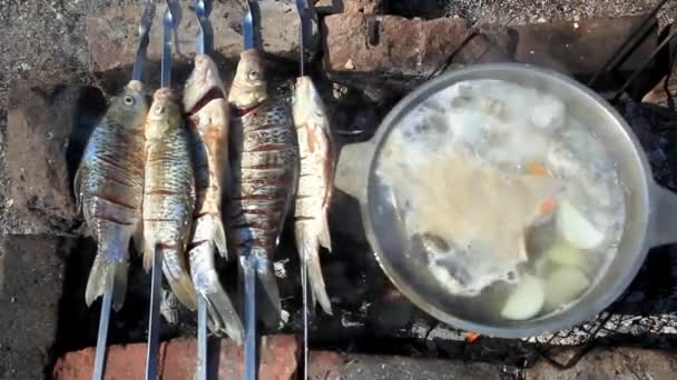fresh fish soup is boiling on a fire and fried Fish on skewers